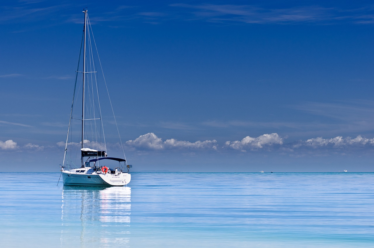 Sail boat out on crystal blue water in the ocean.